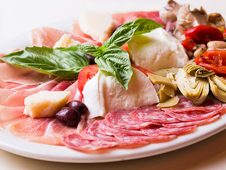 Photo of Antipasto Abbracci for two. The photo shows Italian cold cuts, mozzarella, artichokes, cannellini beans, provolone and parmesan cheese
