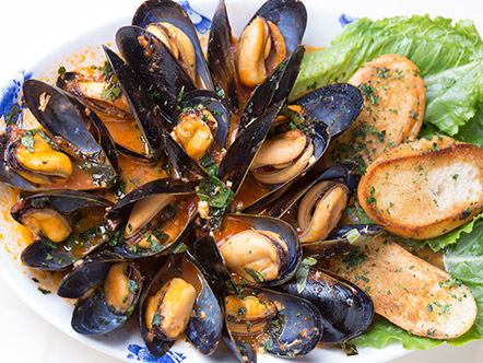 Photo of Caffe Abbracci's mussels in white sauce with crostini on a bed of romaine lettuce