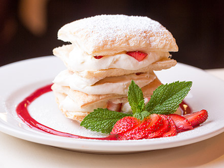 Photo of Caffe Abbracci's signature desert, the Napoleon, layers of crisp puff pastry filled with whipped-vanilla cream. A stream of strawberry coulis and sliced strawberries are visible