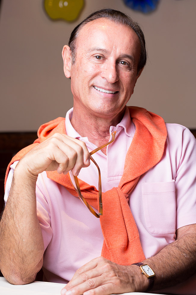 Photo of owner, Nino Pernetti, smiling in a pink polo shirt with a salmon-colored sweater loosely tied over his shoulders