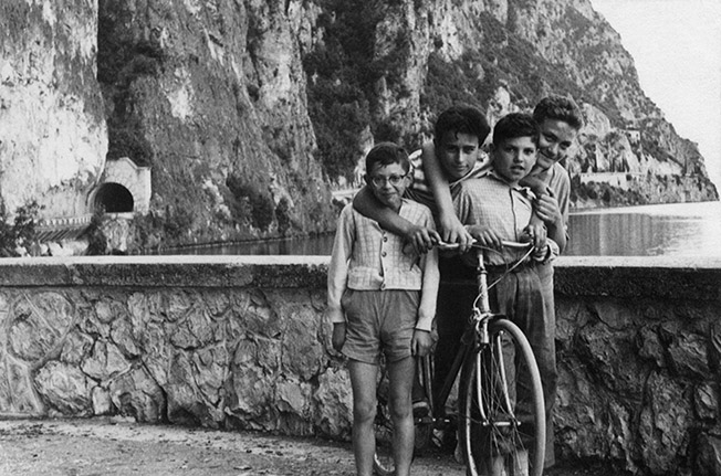 Old black and white photo of Nino as a young boy with his cousins and a bicycle with mountains and a lake in the background