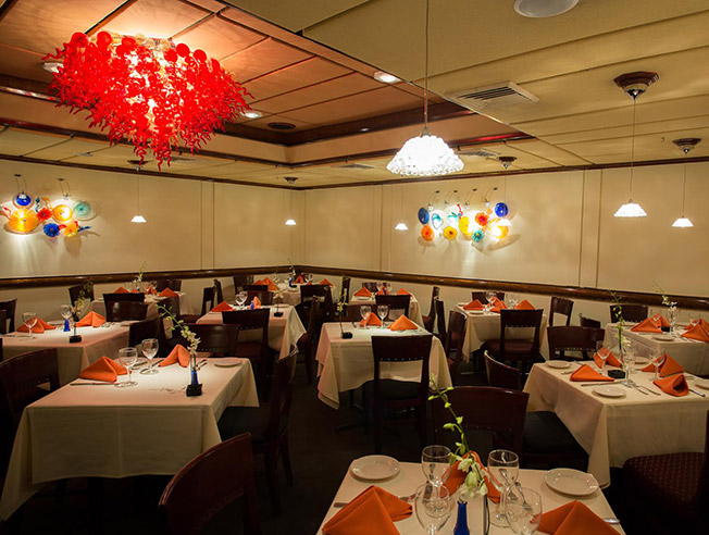 Photo of the private dining room with empty tables set with white table cloths and orange linen napkins. A striking Venetian glass chandelier is visible